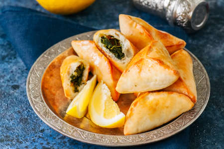 Fatayer sabanekh - traditional arabic spinach triangle hand pies in a vintage plate on a blue stone background.  Close up.