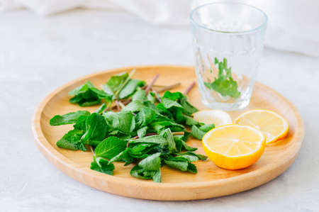Ingredients for moroccan tea or infused water. Mint leaves slices of lemon on a wooden plate. White background. Close up.
