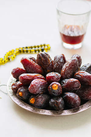 Medjoul - dried dates or kurma in a vintage plate and tea.