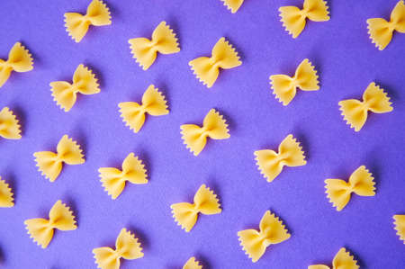 Diagonals of farfalle pasta on a violet background.