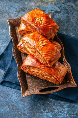 Traditional turkish pastry roll with chocolate and nuts filling - pastich served on a vintage tray.   Stock Photo