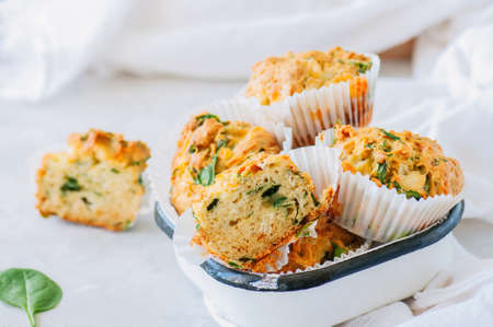 Savory potato spinach and feta muffins in a bowl. White stone background.