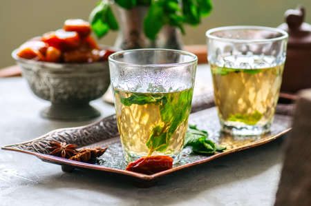 Traditional moroccan mint tea with dates on a vintage tray. White stone background. Stock Photo