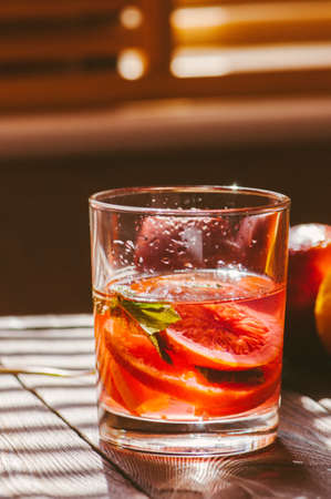 Refreshing blood orange water or infused water in a glass on a wooden background.