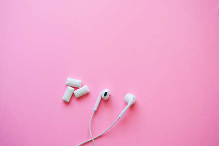 Headphones and menthol bubble gums on a pink background. Relaxation, life style concept. Copy space and top view.
