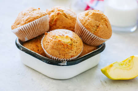 Gluten free almond flour muffins with apples in a bowl on a white stone background. Фото со стока