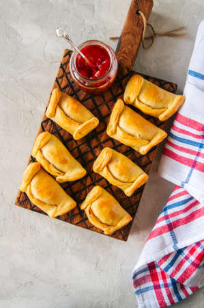 Top view of chilean empanadas on a wooden plate with ketchup. White stone background. Stockfoto