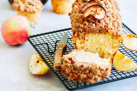Homemade apple crumble cake served on a wire rack on a white sto