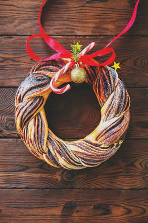 Chocolate swirl brioche wreath with red bow and balls. Stock Photo
