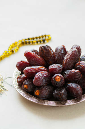 Medjoul - dried dates or kurma in a vintage plate and rosary. Close up.