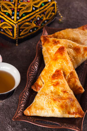 Freshly baked eastern samsa on a vintage tray. Close up.Traditional eastern pastry - samsa filled with meat.
