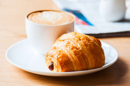 One cup of coffee and croissant on a white plate