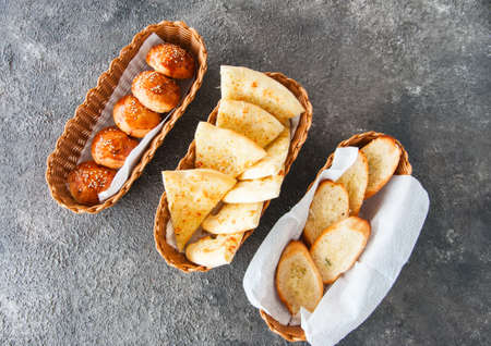 Variety bread snacks in a basket. Burger buns, focaccia, croutons and bruschetta. Top view.