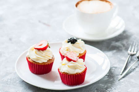 Three delicious cupcakes with berries in a plate. Close up.