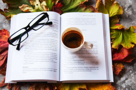 Eye glasses, book and cup of espresso on a maple leaves