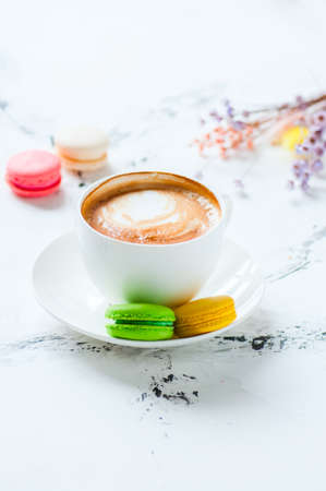 One cup of cappuccino and macarons on a white background. 写真素材