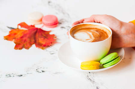 One cup of cappuccino and macarons on a white background. Stock fotó