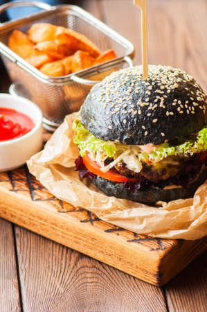 Black burger in a parchment paper on a wooden background. Close up. Reklamní fotografie