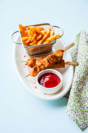 Baked chicken kebabs In a plate with potato fries and ketchup. Close up. Foto de archivo - 135481909