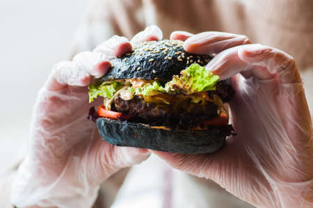 Black burger in a hands of hipster. Close up. Fast or junk food concept.