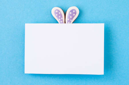 Easter background concept. Easter bunny ears under white empty paper on blue background.