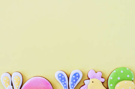 Easter background concept. Colored easter cookies on yellow background. Top view.