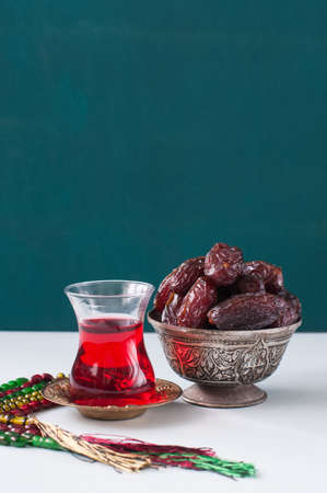 Dry medjoul dates in a vintage bowl with turkish tea in a glass. Close up.
