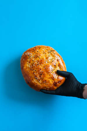Ramadan pide in a hand with medical gloves. Stay ay home or food delivery or social distancing concept.