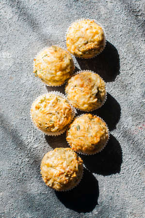 Savory spring herbs and cheese muffins in a bowl. Grey stone background.