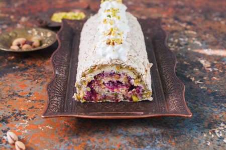 Homemade meringue roll with pistachios berry jam and cream cheese filling. Close up.