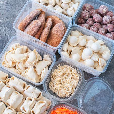 Assortment of Pocket items. Semifinished meatballs, dumplings, pierogi in plastic containers. Archivio Fotografico