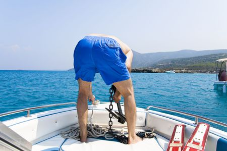 anchoring: Back of man anchoring the boat