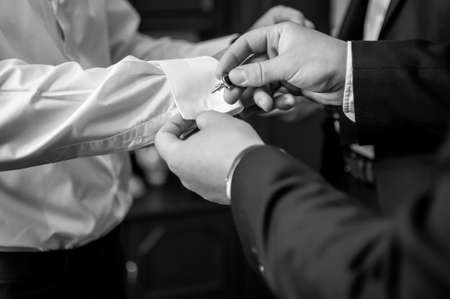 A groom fastening a cuff-link before getting married