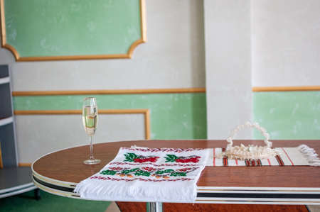 a glass of champagne and an embroidered towel stands on the table