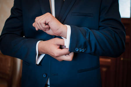 A groom fastening a cuff-link on the shirt