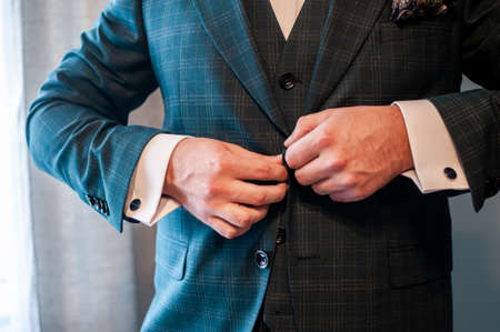 groom buckles the button on his jacket