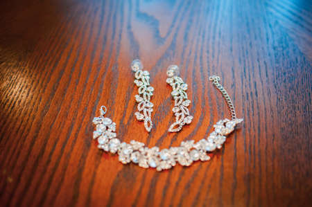 Brides white earrings and abracelet laying on the brown table