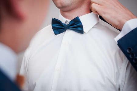 Dark blue bowtie on the grooms neck