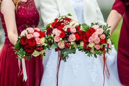 Bouquets de fleurs dans les mains de la mariée et des demoiselles d'honneur