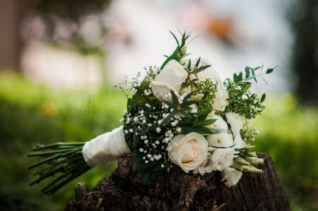 The bride's bouquet of white roses and green leaves, beautifully decorated with white satin ribbon, lies on the grass on a summer day. Wedding theme.