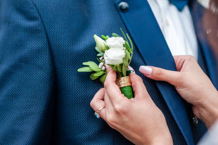 Woman wearing boutonniere on the groom Standard-Bild