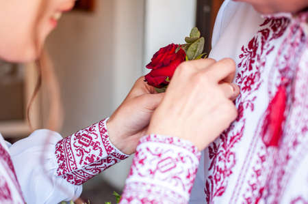 Girl dresses groom boutonniere on the shirt
