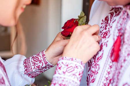 La fille habille la boutonnière du marié sur la chemise