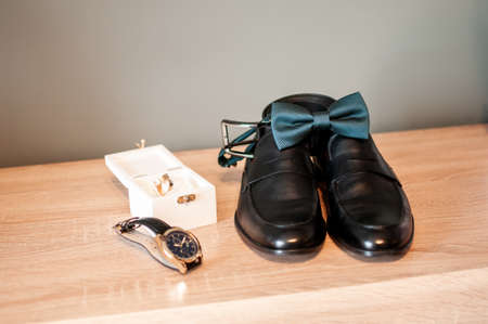 Pair of shoes gold wedding rings and blue tiebow