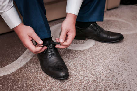White man puts black shoes on the white background 写真素材 - 146181691