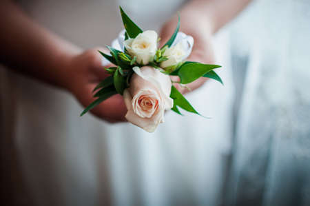 White and pink rose boutonniere in the bride hand