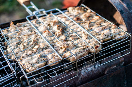 cooking raw meat in a grid on the barbeque grill