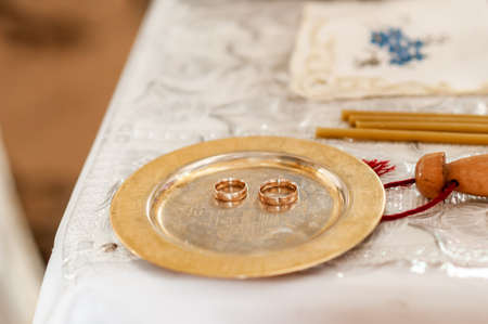 Pair of gold wedding rings on the golden plate