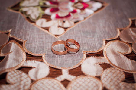 Pair of gold wedding rings on the tablecloth