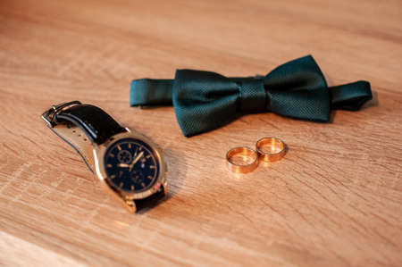 bow tie and pair of gold wedding rings